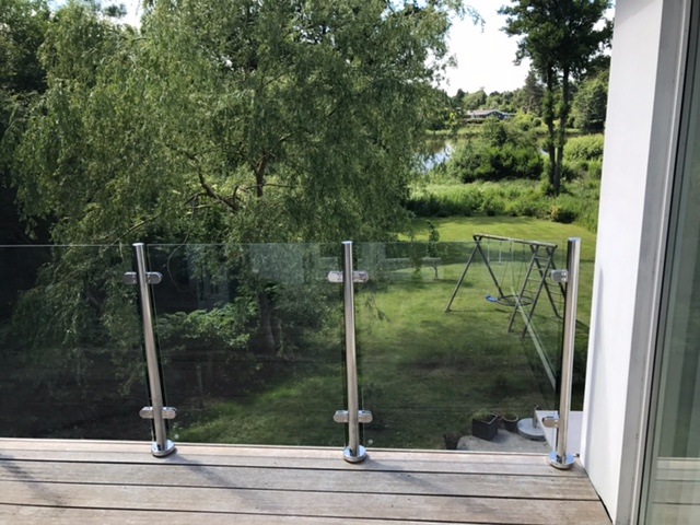 Glasgelænder med rustfrie balustre på hævet terrasse